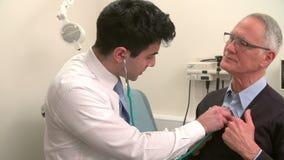 Γιατρός που ακούει το στήθος του ανώτερου αρσενικού ασθενή απόθεμα βίντεο