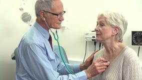 Γιατρός που ακούει το στήθος του ανώτερου θηλυκού ασθενή απόθεμα βίντεο