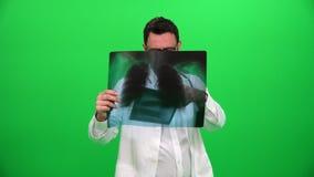 Γιατρός που αναλύει την ακτίνα X στην πράσινη οθόνη απόθεμα βίντεο