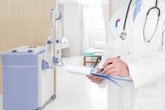 Γιατρός που γράφει μια ιατρική συνταγή με το ιατρικό υπόβαθρο στοκ εικόνες με δικαίωμα ελεύθερης χρήσης