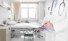 Γιατρός που γράφει μια ιατρική συνταγή στο δωμάτιο νοσοκομείων στοκ εικόνα