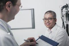 Γιατρός που γράφει στο ιατρικό διάγραμμα με έναν χαμογελώντας ασθενή Στοκ εικόνα με δικαίωμα ελεύθερης χρήσης