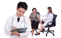 Γιατρός που γράφει την ιατρική έκθεση με το θηλυκό γιατρό που μετρά το bloo στοκ φωτογραφία