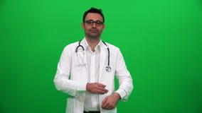 Γιατρός που γυρίζει και που εξετάζει τη κάμερα στο πράσινο υπόβαθρο κιβωτίων φιλμ μικρού μήκους