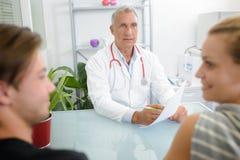 Γιατρός που δίνει τις καλές ειδήσεις στο νέο ζεύγος στοκ εικόνες με δικαίωμα ελεύθερης χρήσης