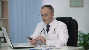 Γιατρός που διαβάζει το ιατρικό βοηθητικό βιβλίο στην ειδική εφαρμογή στο smartphone του απόθεμα βίντεο