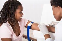 Γιατρός που εγχέει τον ασθενή με τη σύριγγα για να συλλέξει το αίμα Στοκ Φωτογραφίες