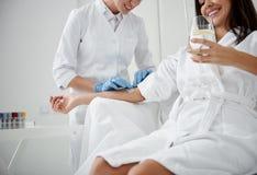 Γιατρός που ελέγχει την ενδοφλέβια σταλαγματιά σε ετοιμότητα γυναικείο ενώ αυτή πόσιμο νερό στοκ φωτογραφίες