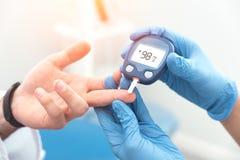 Γιατρός που ελέγχει το επίπεδο ζάχαρης αίματος με το glucometer στοκ εικόνες