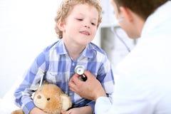 Γιατρός που εξετάζει έναν ασθενή παιδιών από το στηθοσκόπιο Στοκ εικόνες με δικαίωμα ελεύθερης χρήσης