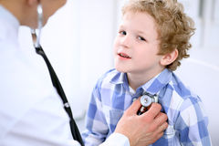 Γιατρός που εξετάζει έναν ασθενή παιδιών από το στηθοσκόπιο στοκ εικόνα