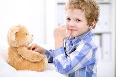 Γιατρός που εξετάζει έναν ασθενή παιδιών από το στηθοσκόπιο στοκ εικόνες