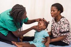 Γιατρός που εξετάζει ένα υπομονετικό παιδί στα μάτια στοκ φωτογραφία