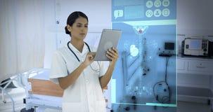 Γιατρός που εξετάζει τα ψηφιακά παραγμένα ιατρικά εικονίδια στην ταμπλέτα απόθεμα βίντεο