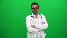 Γιατρός που εξετάζει τη κάμερα στο πράσινο υπόβαθρο απόθεμα βίντεο