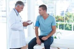 Γιατρός που εξετάζει τη πίεση του αίματος ασθενών του Στοκ Φωτογραφία