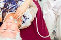 Γιατρός που εξετάζει τον ανώτερο ασθενή με υπερηχητικό στοκ φωτογραφία