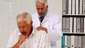 Γιατρός που εξετάζει τον ανώτερο ασθενή του που έχει έναν βήχα απόθεμα βίντεο