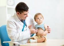 Γιατρός που εξετάζει τον κτύπο της καρδιάς του αγοριού παιδιών με στοκ εικόνα με δικαίωμα ελεύθερης χρήσης