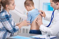 Γιατρός που εξετάζει το βήχοντας μικρό παιδί στοκ εικόνες