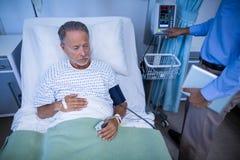 Γιατρός που εξετάζει το ποσοστό καρδιών ασθενή στοκ εικόνα