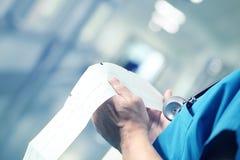 Γιατρός που εξετάζει ECG στο διάδρομο νοσοκομείων Στοκ Εικόνες
