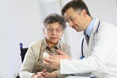 Γιατρός που εξηγεί σε μια ηλικιωμένη γυναίκα τη χρήση των φαρμάκων στοκ εικόνα