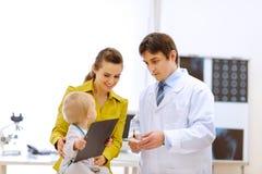 γιατρός που εξηγεί στον παιδίατρο μητέρων κάτι Στοκ Φωτογραφία