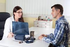 Γιατρός που εξηγεί τα αποτελέσματα ακτίνας X πνευμόνων στο μέσο ηλικίας ασθενή στη διαβούλευση του δωματίου στοκ εικόνα