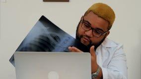 Γιατρός που εξηγεί τα των ακτίνων X αποτελέσματα στον ασθενή μέσω της τηλεοπτικής κλήσης στο lap-top απόθεμα βίντεο