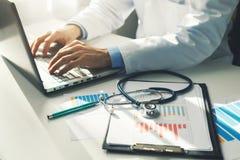 Γιατρός που εργάζεται με τις ιατρικές στατιστικές και τις οικονομικές εκθέσεις στοκ εικόνα με δικαίωμα ελεύθερης χρήσης