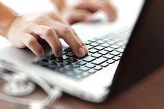 Γιατρός που εργάζεται με το φορητό προσωπικό υπολογιστή στον ιατρικό χώρο εργασίας Στοκ φωτογραφία με δικαίωμα ελεύθερης χρήσης