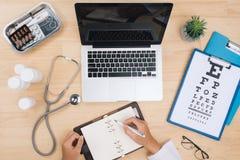 Γιατρός που εργάζεται στον πίνακα γραφείων με το στηθοσκόπιο και το σημειωματάριο με Στοκ Εικόνες
