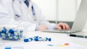 Γιατρός που εργάζεται στο νοσοκομείο Χάπια που ανατρέπονται στο γραφείο γιατρών ` s Στοκ Εικόνες