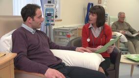 Γιατρός που ελέγχει στον αρσενικό ασθενή που έχει τη χημειοθεραπεία απόθεμα βίντεο
