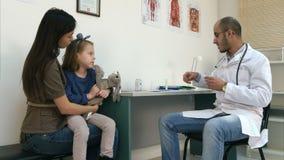 Γιατρός που ελέγχει τη θερμοκρασία στο θερμόμετρο και που συμπληρώνει την ιατρική μορφή απόθεμα βίντεο