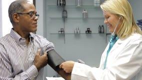 Γιατρός που ελέγχει τη πίεση του αίματος του αρσενικού ασθενή φιλμ μικρού μήκους
