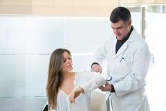Γιατρός που ελέγχει τον αγκώνα με το ανακλαστικό στρογγυλό σφυρί στη γυναίκα Στοκ εικόνες με δικαίωμα ελεύθερης χρήσης