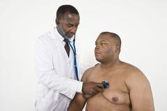 Γιατρός που ελέγχει τον κτύπο της καρδιάς ενός παχύσαρκου ασθενή στοκ φωτογραφίες