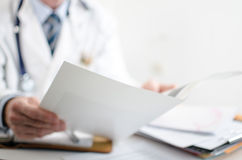Γιατρός που διαβάζει τις ιατρικές σημειώσεις Στοκ φωτογραφία με δικαίωμα ελεύθερης χρήσης