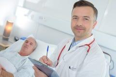 Γιατρός που καθιστά τις σημειώσεις υπομονετικές στο υπόβαθρο στοκ εικόνες