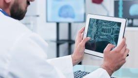 Γιατρός που κοιτάζει και που αναλύει την ακτίνα X σε μια ψηφιακή οθόνη PC ταμπλετών απόθεμα βίντεο