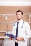 Γιατρός που κρατά έναν φάκελλο στα χέρια με το στηθοσκόπιο arround το ΝΕ του Στοκ Εικόνα