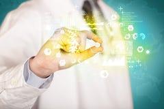Γιατρός που κρατά ένα χάπι μεταξύ των δάχτυλων Στοκ Εικόνες