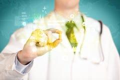 Γιατρός που κρατά ένα χάπι μεταξύ των δάχτυλων Στοκ Εικόνα