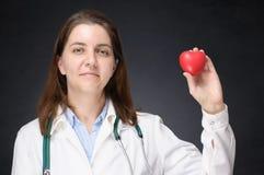 Γιατρός που κρατά μια κόκκινη μορφή καρδιών Στοκ Φωτογραφία