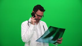 Γιατρός που κρατά τα των ακτίνων X αποτελέσματα και που μιλά στο τηλέφωνο σε μια πράσινη οθόνη απόθεμα βίντεο