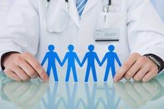 Γιατρός που κρατά την μπλε αλυσίδα ανθρώπων εγγράφου στο γραφείο Στοκ φωτογραφία με δικαίωμα ελεύθερης χρήσης