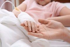Γιατρός που κρατά το χέρι λίγου παιδιού με την ενδοφλέβια σταλαγματιά στο νοσοκομείο στοκ εικόνες