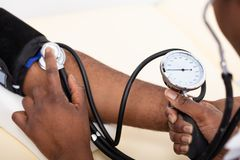 Γιατρός που μετρά τη πίεση του αίματος του ασθενή στοκ φωτογραφίες με δικαίωμα ελεύθερης χρήσης